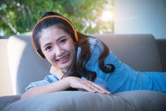 Jonge gelukkige vrouw die op bank het luisteren muziek met oortelefoons liggen stock afbeelding