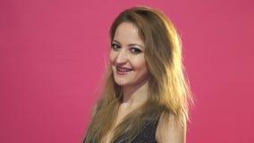 Jonge gelukkige vrouw die op een roze achtergrond knipogen stock footage