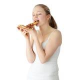 Jonge gelukkige vrouw die pizza eet royalty-vrije stock foto's