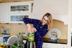 Jonge gelukkige vrouw die smoothie cocktail in mixer voorbereiden royalty-vrije stock foto