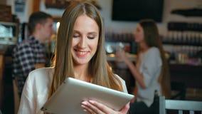 Jonge gelukkige vrouw die tabletcomputer in een koffie met behulp van stock videobeelden