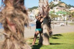 Jonge gelukkige vrouw die tegen boom op strand leunen Stock Afbeeldingen