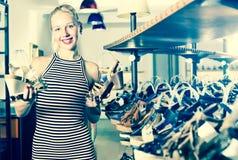 Jonge gelukkige vrouw die van twee paren schoenen kiezen Royalty-vrije Stock Afbeeldingen