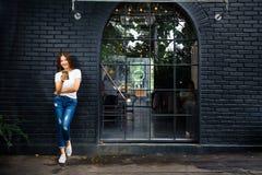 Jonge gelukkige vrouw die zich buiten een koffiewinkel bevinden die haar telefoon met behulp van Royalty-vrije Stock Foto's