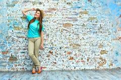 Jonge gelukkige vrouw die zich tegen bakstenen muur bevinden stock fotografie