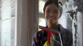 Jonge gelukkige vrouw het afvegen glasoppervlakte na nevel, het schoonmaken de dienstkwaliteit stock fotografie