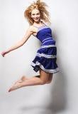 Jonge gelukkige vrouw in het blauwe kleding springen stock foto