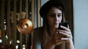 Jonge gelukkige vrouw in hoedenzitting in koffie en het gebruiken van smartphone Mooi wijfje die Internet surfen stock footage