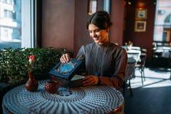 Jonge gelukkige vrouw in koffie met kist en juwelen Stock Foto