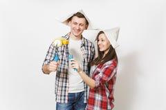 Jonge gelukkige vrouw, man die in vrijetijdskleding verfrollen voor muurschilderij houden Paar op witte achtergrond wordt geïsole royalty-vrije stock foto