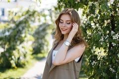 Jonge gelukkige vrouw met een prachtige glimlach in een modieus beige vest in een witte T-shirt die in openlucht stellen stock fotografie