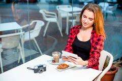 Jonge gelukkige vrouw met een tabletzitting in koffie Stock Afbeeldingen