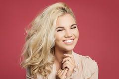 Jonge gelukkige vrouw met kapsel dat van het blonde het krullende loodje pret heeft en tegen kleurrijke roze muurachtergrond lach royalty-vrije stock afbeelding