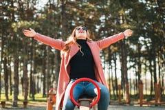 Jonge gelukkige vrouw op het geschommel in de speelplaats stock foto