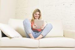 Jonge gelukkige vrouw op huisbank die Internet app op digitaal tabletstootkussen gebruiken royalty-vrije stock afbeelding