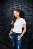 Jonge gelukkige vrouw status die tegen donkere bakstenen muur leunen liste Royalty-vrije Stock Afbeelding