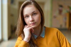 Jonge gelukkige vrouwelijke studentzitting in de gang op haar school stock afbeelding