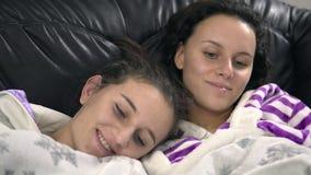 Jonge gelukkige vrouwelijke zusters die op TV op een bank letten Stock Afbeeldingen