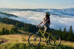Jonge gelukkige vrouwen berijdende fiets in de bergen bij de zomerdag royalty-vrije stock foto