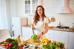 Jonge gelukkige vrouwen scherpe kool voor binnen het maken van salade in de mooie keuken met groene verse ingrediënten gezond voe stock afbeelding