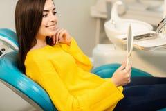 Jonge gelukkige vrouwencli?nt die de spiegel met toothy glimlach op het tandkantoor bekijken stock fotografie