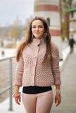 Jonge gelukkige vrouwenstijging dichtbij vuurtoren, gelukkig, vers en glimlachen, gekleed in toevallige zachte roze sweater stock foto