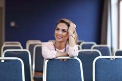 Jonge gelukkige vrouwenzitting alleen in conferentieruimte Stock Fotografie