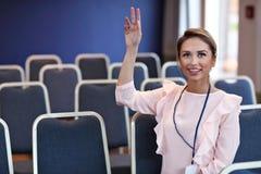 Jonge gelukkige vrouwenzitting alleen in conferentieruimte Stock Afbeeldingen