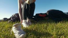 Jonge gelukkige vrouwenzitting op het gras met de jonge mens en veranderingen haar tennisschoenen in zonnige dag stock video