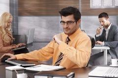 Jonge gelukkige zakenman, die bij het bureau werkt Royalty-vrije Stock Afbeeldingen