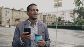 Jonge gelukkige zakenman gebruikend smartphone en in openlucht lopend met kop van koffie Royalty-vrije Stock Afbeelding