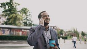 Jonge gelukkige zakenman gebruikend smartphone en in openlucht lopend met kop van koffie Stock Fotografie