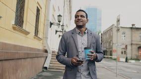 Jonge gelukkige zakenman gebruikend smartphone en in openlucht lopend met kop van koffie Stock Afbeeldingen