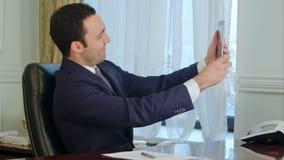 Jonge gelukkige zakenmanmens die grappige selfies met digitale tablet in het bureau nemen stock videobeelden