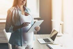 Jonge Gelukkige Zwangere Vrouw die Digitale Tablet gebruiken royalty-vrije stock fotografie