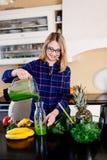 Jonge gelukkige zwangere vrouw die groene smoothie gieten aan glaskop stock afbeelding