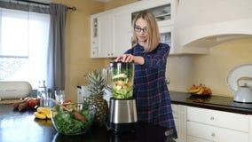 Jonge gelukkige zwangere vrouw die smoothie in mixer voorbereidingen treffen stock videobeelden