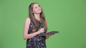 Jonge gelukkige zwangere vrouw die terwijl het gebruiken van digitale tablet denken stock video