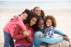 Jonge gemengde rasfamilie die op strand omhelst Stock Foto's