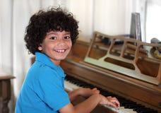 Jonge gemengde rasjongen bij de piano stock fotografie