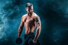 Jonge gescheurde mensenbodybuilder met perfecte abs, schouders, bicepsen, triceps en borst het stellen met een domoor royalty-vrije stock fotografie
