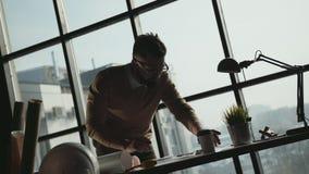 Jonge geschikt architecturale ingenieur die in helder bureau werken stock videobeelden