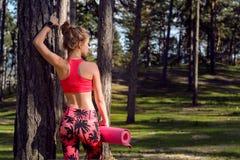 Jonge geschikte atletische vrouw die slim horloge dragen en yogamat, klaar voor haar training in een bosmening en lichaamsgeluk h stock foto's