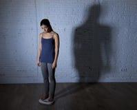 Jonge geschikte en slanke vrouw die lichaamsgewicht controleren op schaal met groot gespannen droevig en wanhopig schaduwlicht Stock Afbeeldingen