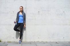 Jonge, geschikte en sportieve vrouw die na de opleiding rusten Fitness, sport, stedelijke jogging en gezond levensstijlconcept stock foto