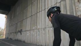 Jonge geschikte mannelijke fietser berijdende fiets uit het zadel die zwarte uitrusting, helm en zonnebril dragen Het cirkelen co stock footage