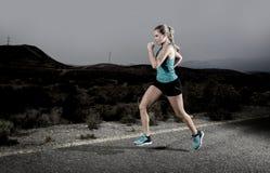 Jonge geschikte sportvrouw die in openlucht op asfaltweg loopt in bergfitness training royalty-vrije stock foto