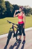 Jonge geschikte sportwoman is te verfrissen drinkwater zich Zij is outsid stock afbeelding