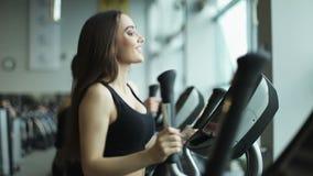 Jonge geschikte vrouw die een elliptische trainer in een geschiktheidscentrum gebruiken stock video