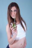 Jonge geschikte vrouw die een glas met kiwistukken houden Royalty-vrije Stock Foto's